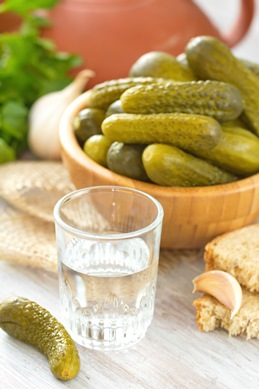 Glass of vodka with pickled cucumbers and garlic on the wooden table