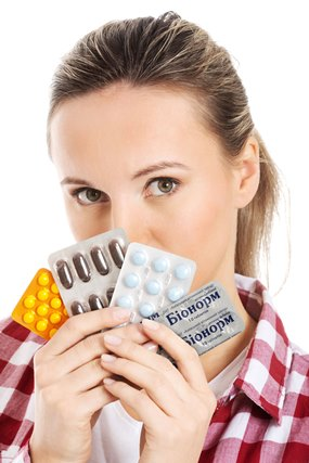 Young casual woman holding pills.