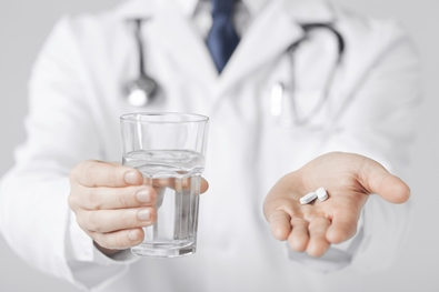 doctor hands giving white pills and glass of water